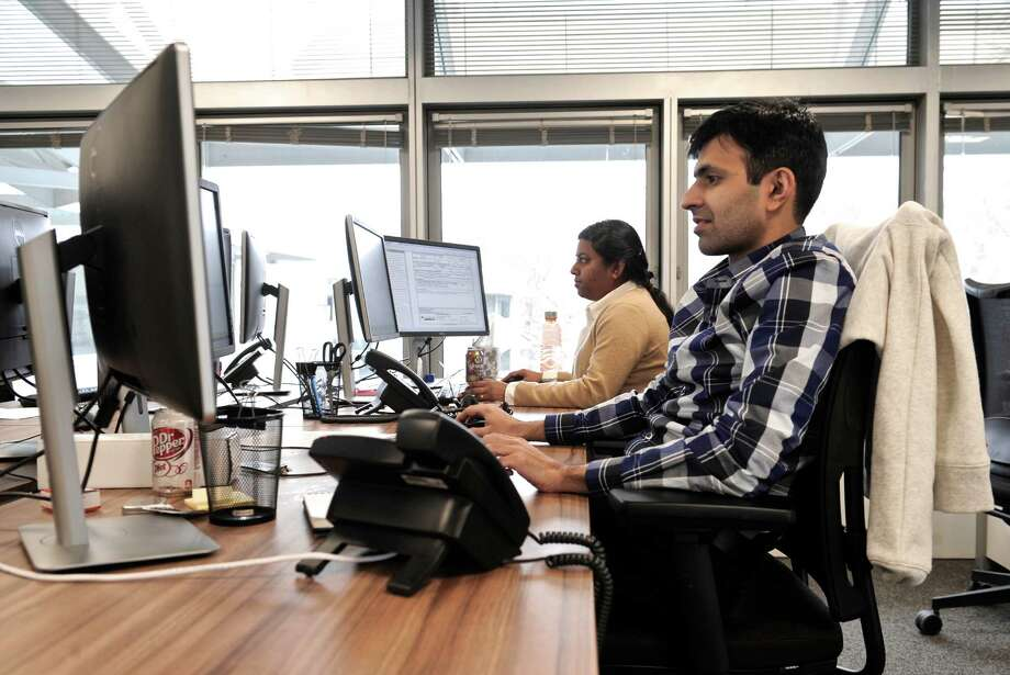 Kashif Qureshi, of Scarsdale, New York, right, a Report Developer and Gokulalakshmi Gangiah, of Danbury, an Analyst, for NewOak, at work in the firms space in the Matrix Corporate Center. Photo: H John Voorhees III / H John Voorhees III / The News-Times