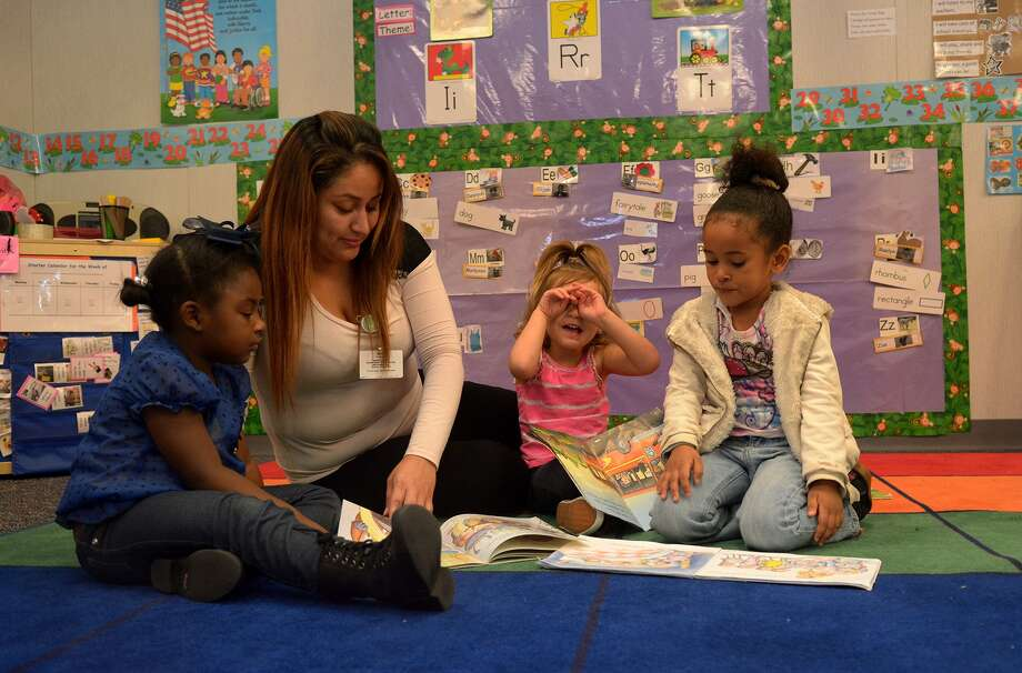 Zoe Banks, 3, from left, teacher Brianda Garcia, Raelyn Caminita, 3, and Lena Walt, 3, share reading time at Humble Head Start Center on Feb. 3, 2016. (Photo by Jerry Baker/Freelance) Photo: Jerry Baker, Freelance