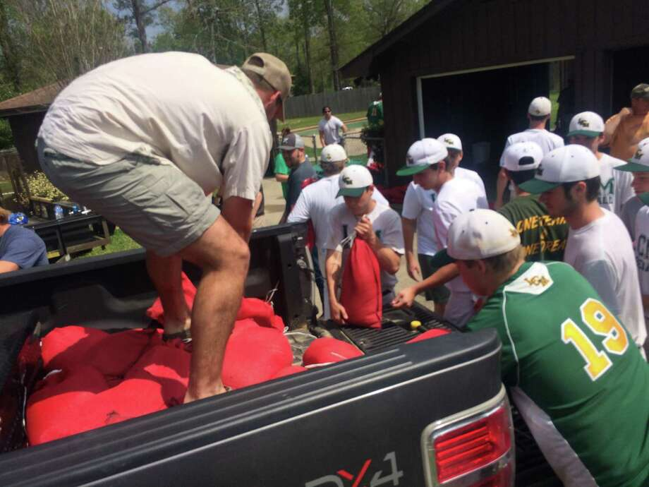 The Little Cypress-Mauriceville High School baseball team unloads 50 sandbags out of the truck bed. On Monday and Tuesday, the team distributed close to 500 bags to 11 homes. Photo: Brooks Kubena/The Enterprise