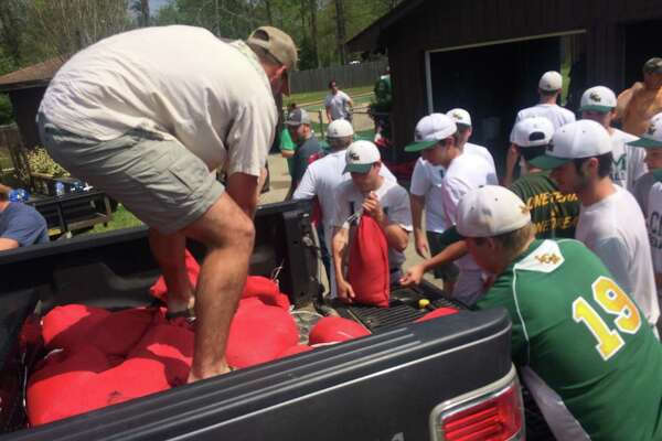 The Little Cypress-Mauriceville High School baseball team unloads 50 sandbags out of the truck bed. On Monday and Tuesday, the team distributed close to 500 bags to 11 homes.