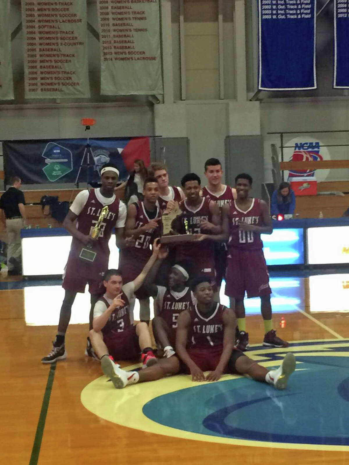 The St. Luke's basketball team poses after winning the NEPSAC Class C title over Pingree 74-68 in overtime.
