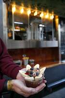 Keith Pape holds an Original Gangster acai bowl ordered from the custom-made Bowl'd Acai food truck in San Francisco, Calif. on Wednesday, March 16, 2016.