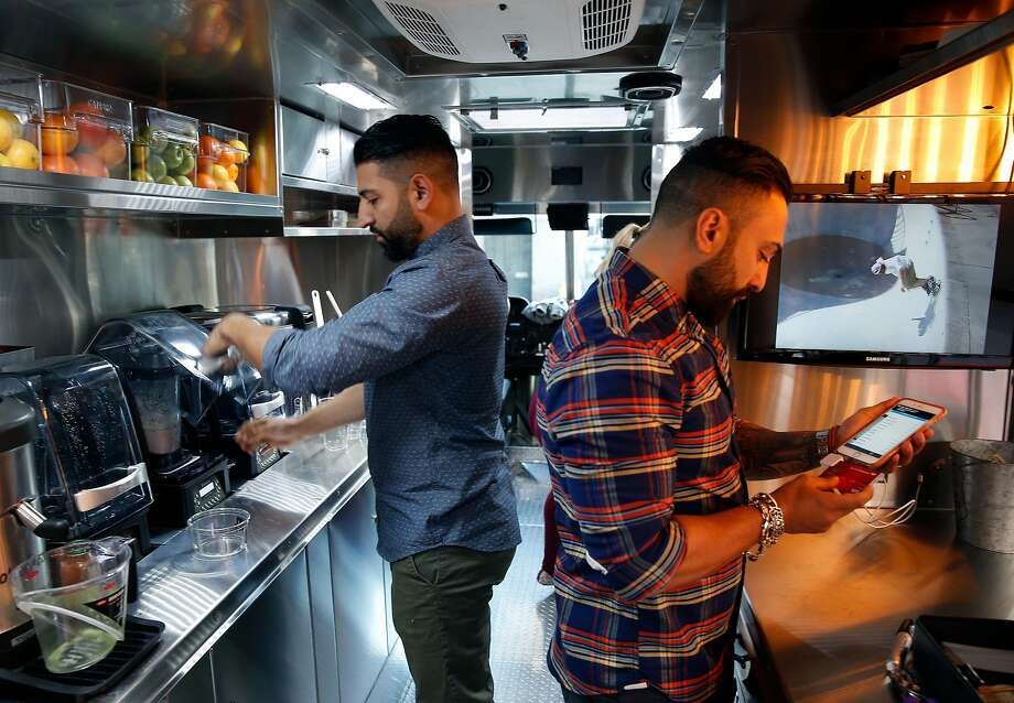 Bowl'd Açai partners Angel Serratos (left) and Reza Morvari fill orders inside their the custom-built food truck. At right, Keith Pape holds an Original Gangster açai bowl. Above, the truck is painted a sleek gunmetal gray to convey a strong presence. Photo: Paul Chinn, The Chronicle