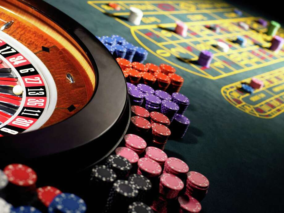 Gambling chips stacked around roulette wheel on gaming table. Photo: Michael Blann, Getty Images / (c) Michael Blann