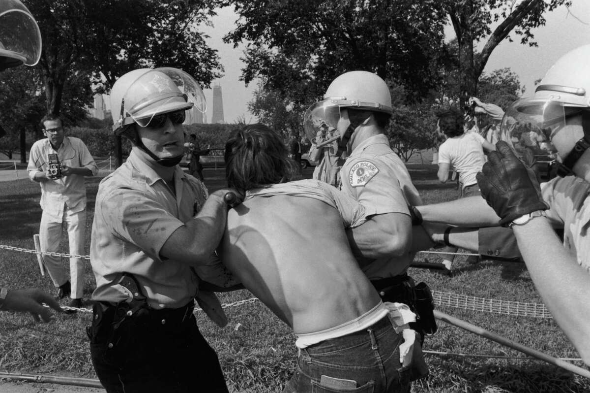 Cigar-smoking police officers arrest a protester at a riot in Grant Park during the Democratic National Convention.