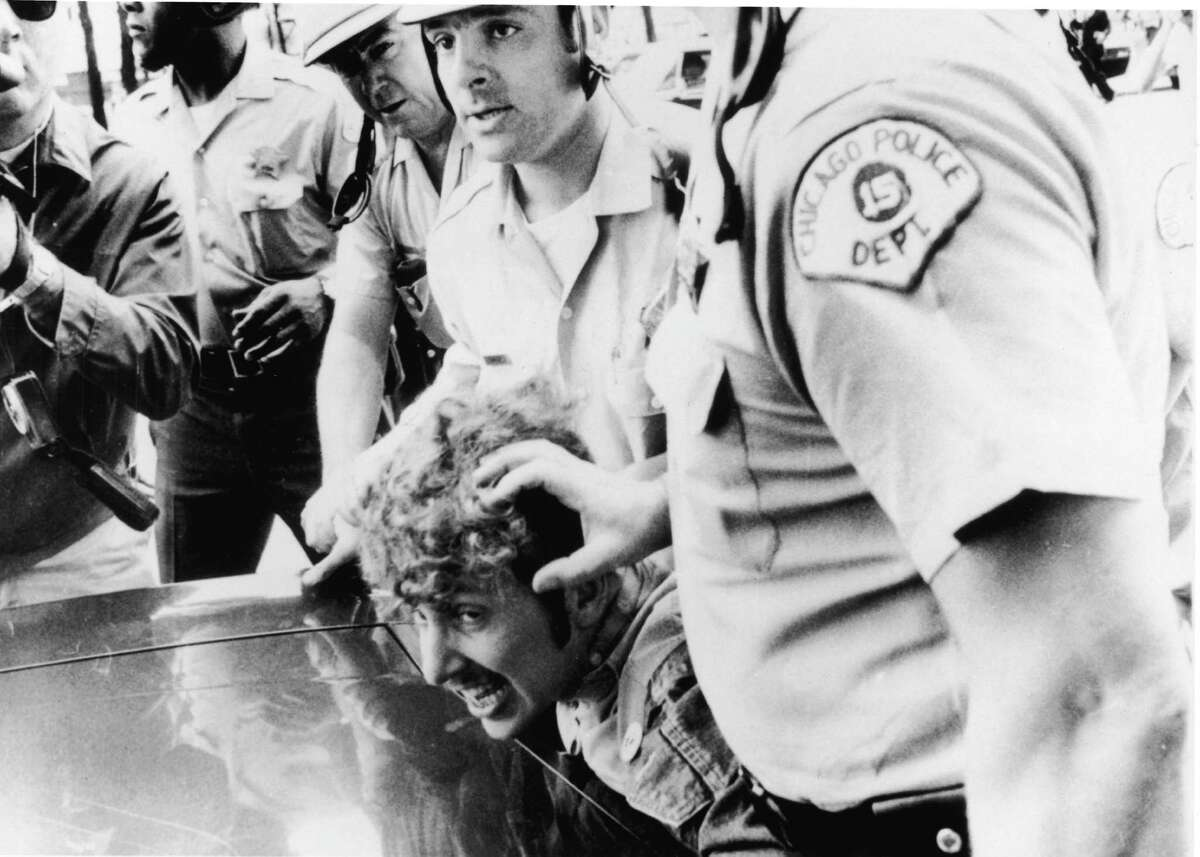 Officers from the Chicago Police Department push a protester's head against the hood of a car as they restrain him after he climbed onto a wooden barricade near the Democratic headquarters of the 1968 Democratic National Convention and waved a Vietcong flag during anti-Vietnam War demonstrations.