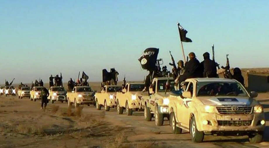 Islamic State militants raise weapons and wave flags as a convoy of vehicles heads to Iraq in 2014. A reader notes that modern notions of warfare make it more difficult to defeat the terrorists. Photo: Uncredited /Associated Press / Militant photo via social media