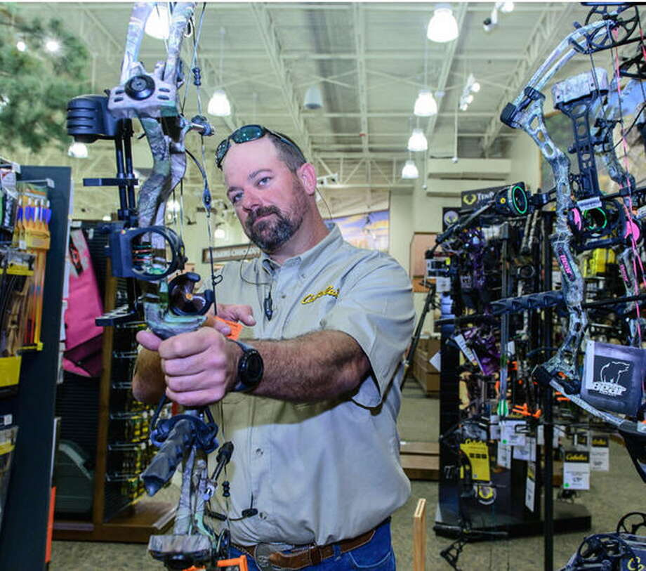 Outfitter Chris Glover shows how to use one of the many bows at the new Cabela's store at 2421 S. Gulf Freeway in League City. The store is set to open March 17.  Outfitter Chris Glover shows how to use one of the many bows at the new Cabela's store at 2421 S. Gulf Freeway in League City. The store is set to open March 17. Photo: Kim Christensen