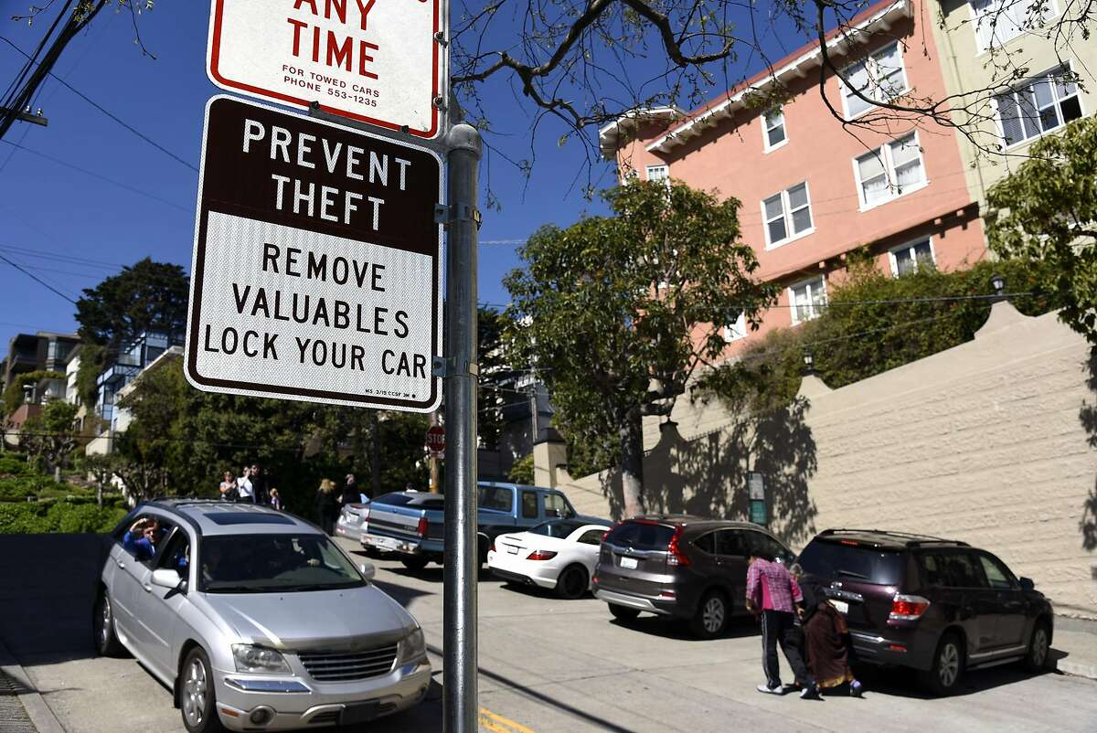 Signs warn tourists not to leave valuables in their cars near crooked Lombard Street in San Francisco on Wednesday, March 16, 2016.