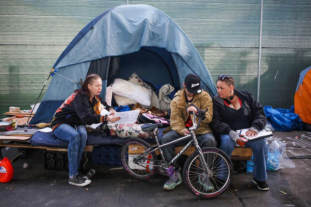 Joolie Coombes (left), Jeremy Harvell and a member of the Homeless Outreach Team are gathered outside a homeless camp tent on Division Street in San Francisco in March 1.