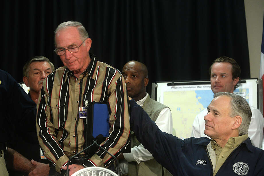 Newton County Judge Truman Dougharty is comforted by Texas Governor Greg Abbott as he becomes emotional reflecting on the devastation to citizens in his county during a press conference at the Emergency Management office in Orange Wednesday.  Photo taken Wednesday, March 16, 2016 Kim Brent/The Enterprise Photo: Kim Brent / Beaumont Enterprise