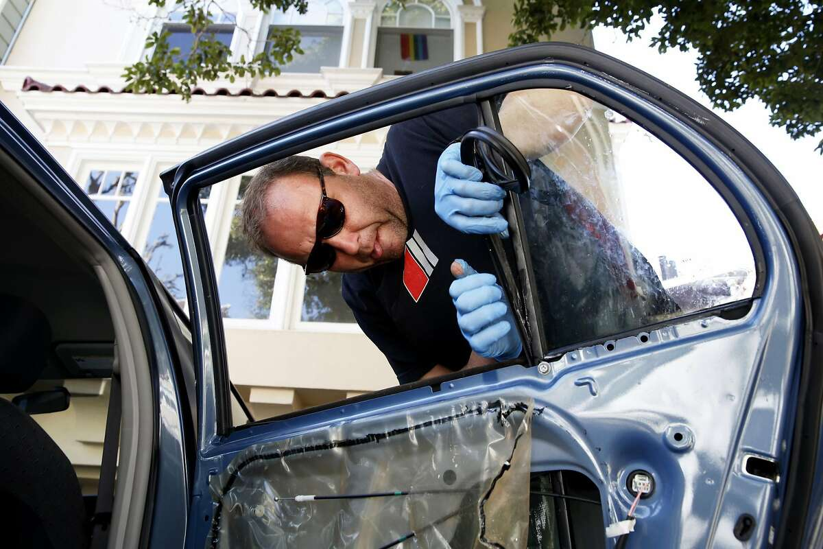 Andrey Snigorenko installs a new window into a Toyota Yaris that was burglarized in San Francisco, California, on Wednesday, March 16, 2016.