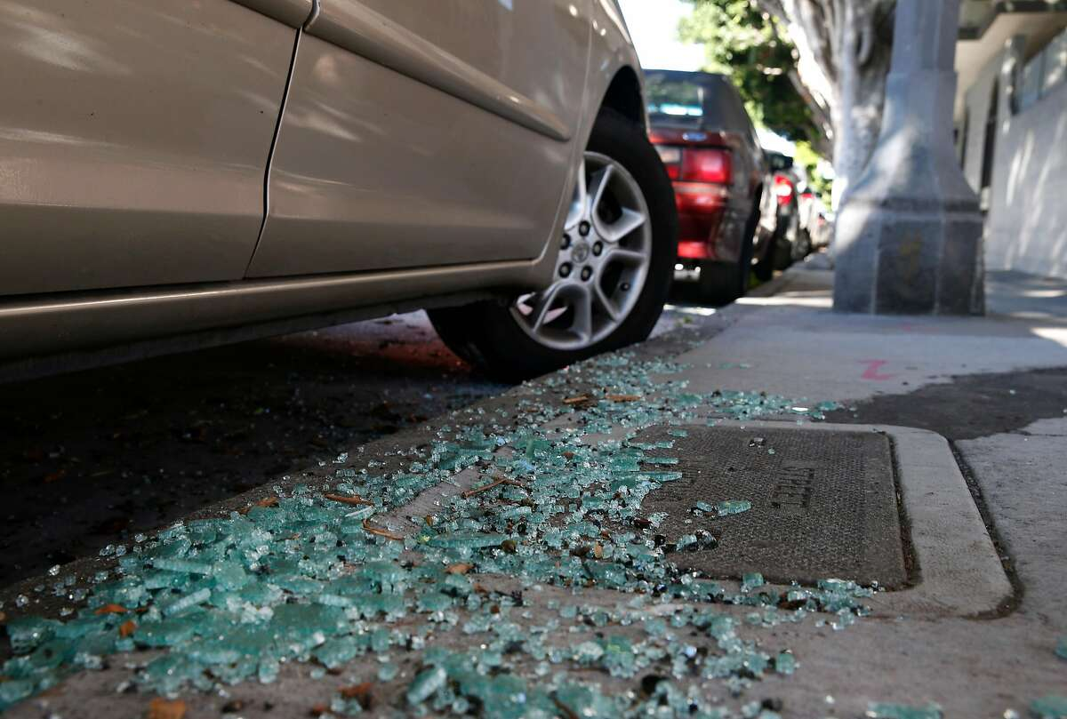Shattered glass from a recent car break-in remains on the sidewalk on Bay Street near Kearny Street in San Francisco.