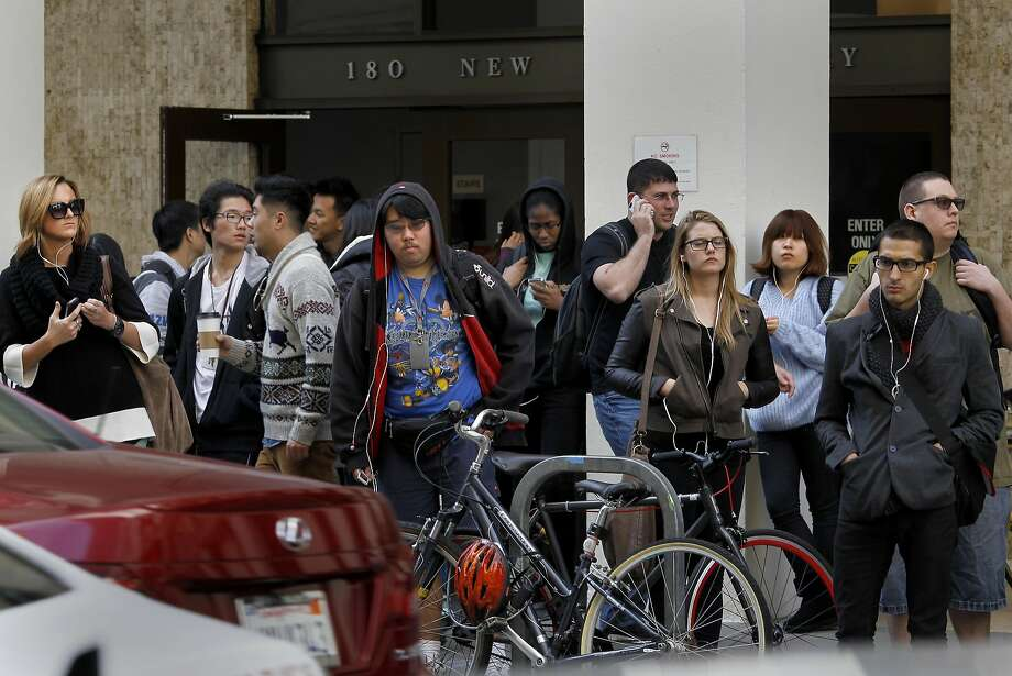 Art students file out of classes at the New Montgomery Street campus to wait for shuttles that crisscross the city. San Francisco City Attorney Dennis Herrera is questioning the possible improper conversion of buildings by the Academy of Art University into student housing and classrooms Tuesday November 13, 2012. Photo: Brant Ward, The Chronicle