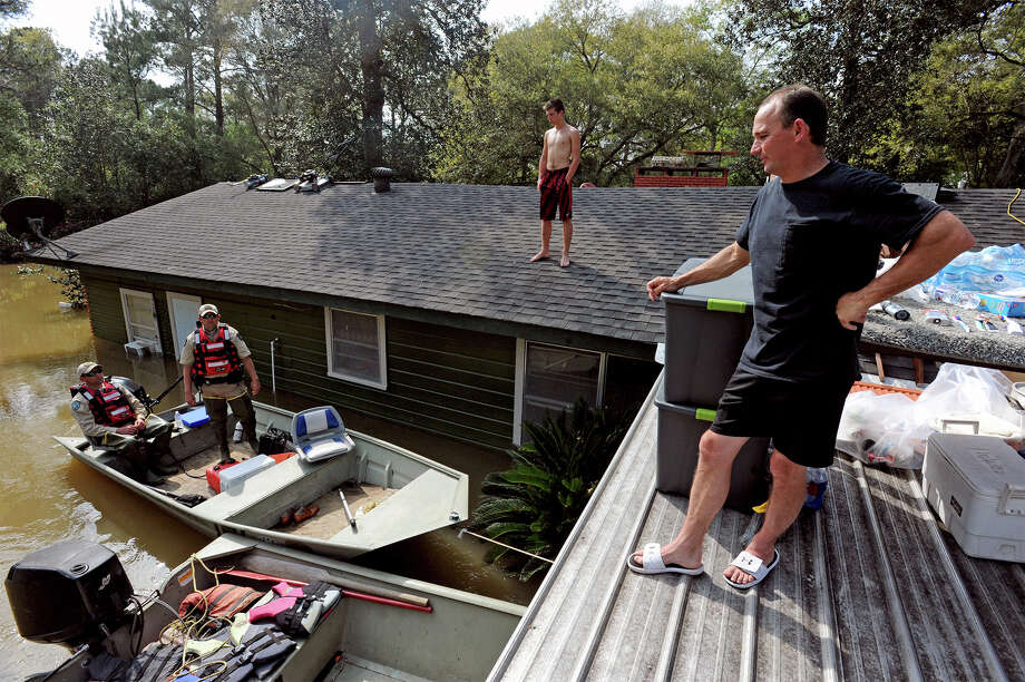 From right, Jamie Holden Sr. and Trent Black, 15, talk to Game Wardens Randy Harper, left, and Chad West from their roof in Deweyville on Wednesday. The family carried many household items and furniture to the roof to prevent evacuation. Items include a washer, dryer, microwave, 65 inch television, grill, generator and an Xbox. Photo taken Wednesday, March 16, 2016 Guiseppe Barranco/The Enterprise Photo: Guiseppe Barranco, Photo Editor