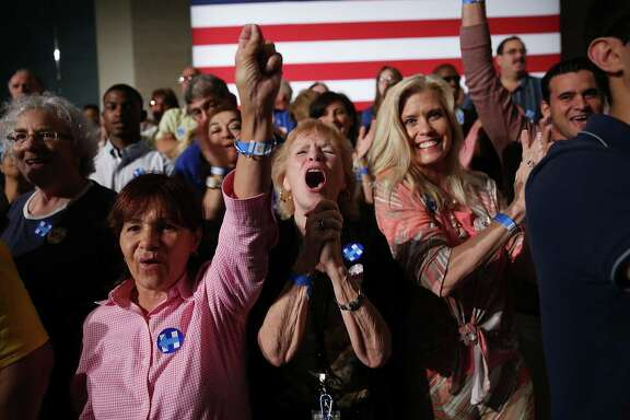 Hillary Clinton supporters react Tuesday to early primary returns in West Palm Beach, Fla. Both Clinton and GOP front-runner Donald Trump now seek to shift the focus to November, partly since their campaigns benefit from a sense of inevitability, especially among undecided voters.