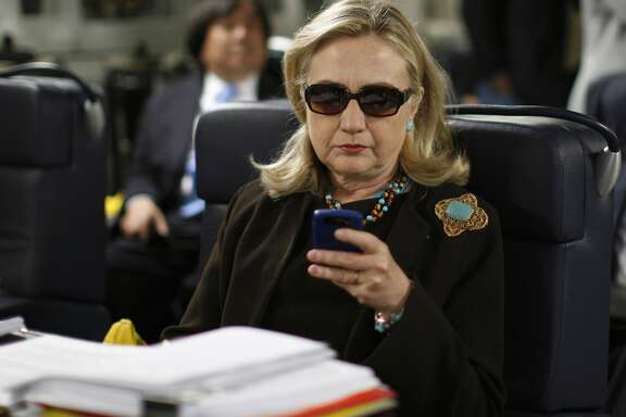 FILE - In this Oct. 18, 2011, file photo, then-Secretary of State Hillary Rodham Clinton checks her Blackberry from a desk inside a C-17 military plane upon her departure from Malta, in the Mediterranean Sea, bound for Tripoli, Libya. Newly released emails show a 2009 request to issue a secure government smartphone to then-Secretary of State Hillary Clinton was denied by the National Security Agency.  (AP Photo/Kevin Lamarque, Pool, File)