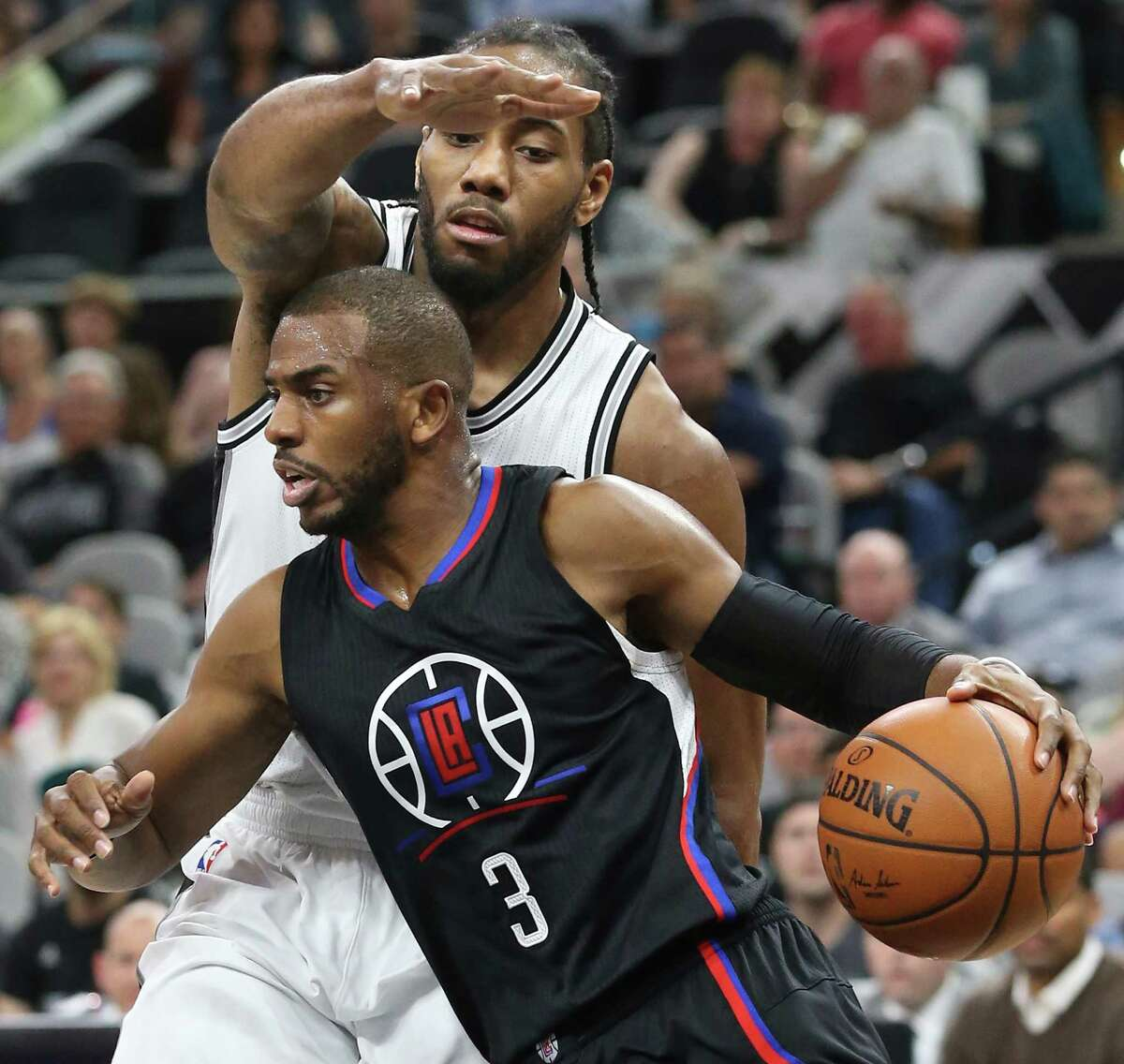Kawhi Leonard attempts to keep a lid on the offensive efforts of Chris Paul as the Spurs host the Clippers at the AT&T Center on March 15, 2016.