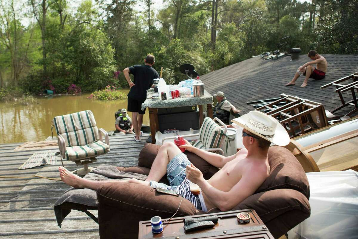 Jamie Holden moved his belongings onto the roof of his home in Deweyville before floodwaters got inside.
