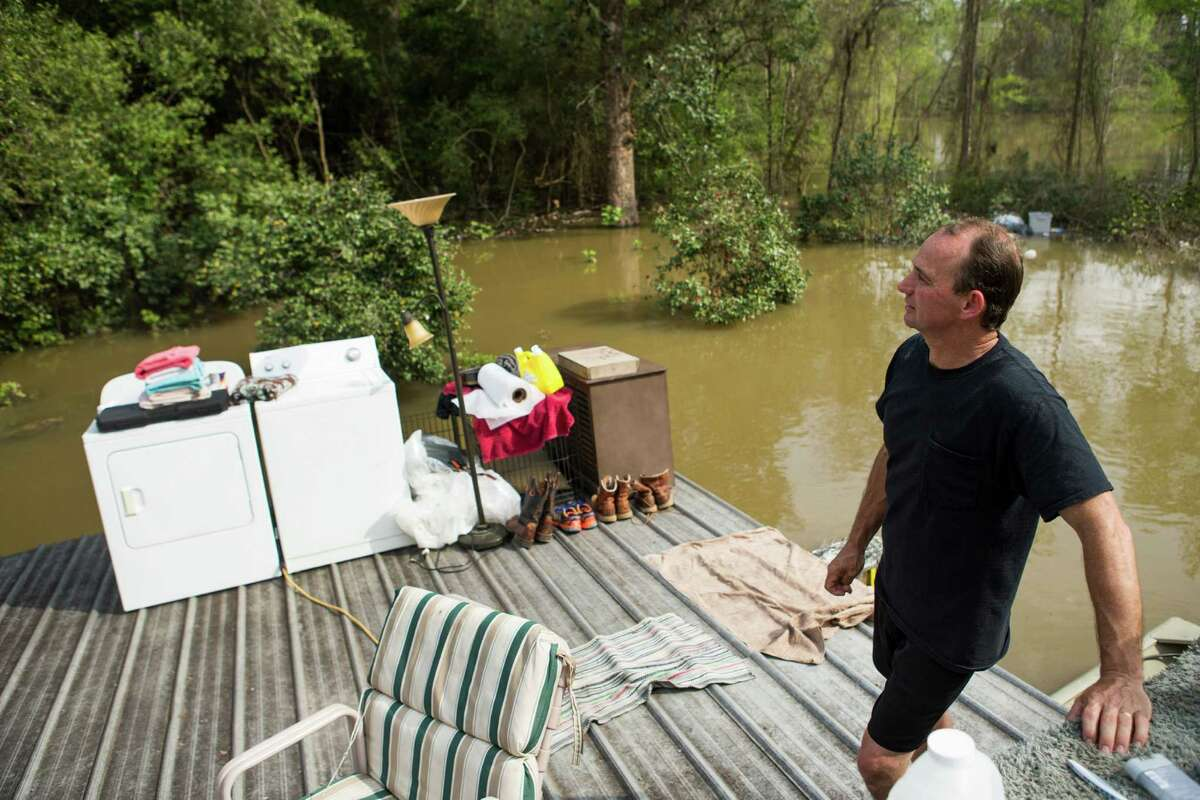 Jamie Holden, Sr., stands on his roof surrounded by floodwaters from the Sabine River on Wednesday, March 16, 2016, in Deweyville, Texas. Holden moved his belongings onto his roof before floodwater got inside his house. Swollen waterways have displaced thousands of people in flood-ravaged communities in Southeast Texas and floodwaters are forecast to rise even more. (Brett Coomer/Houston Chronicle via AP) MANDATORY CREDIT