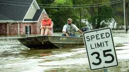 Danielle Henry, left, and Beau Burch ride in a boat through floodwaters from the Sabine River, Wednesday, March 16, 2016, in Deweyville, Texas. Swollen waterways have displaced thousands of people in flood-ravaged communities in Southeast Texas and floodwaters are forecast to rise even more. (Brett Coomer/Houston Chronicle via AP) MANDATORY CREDIT