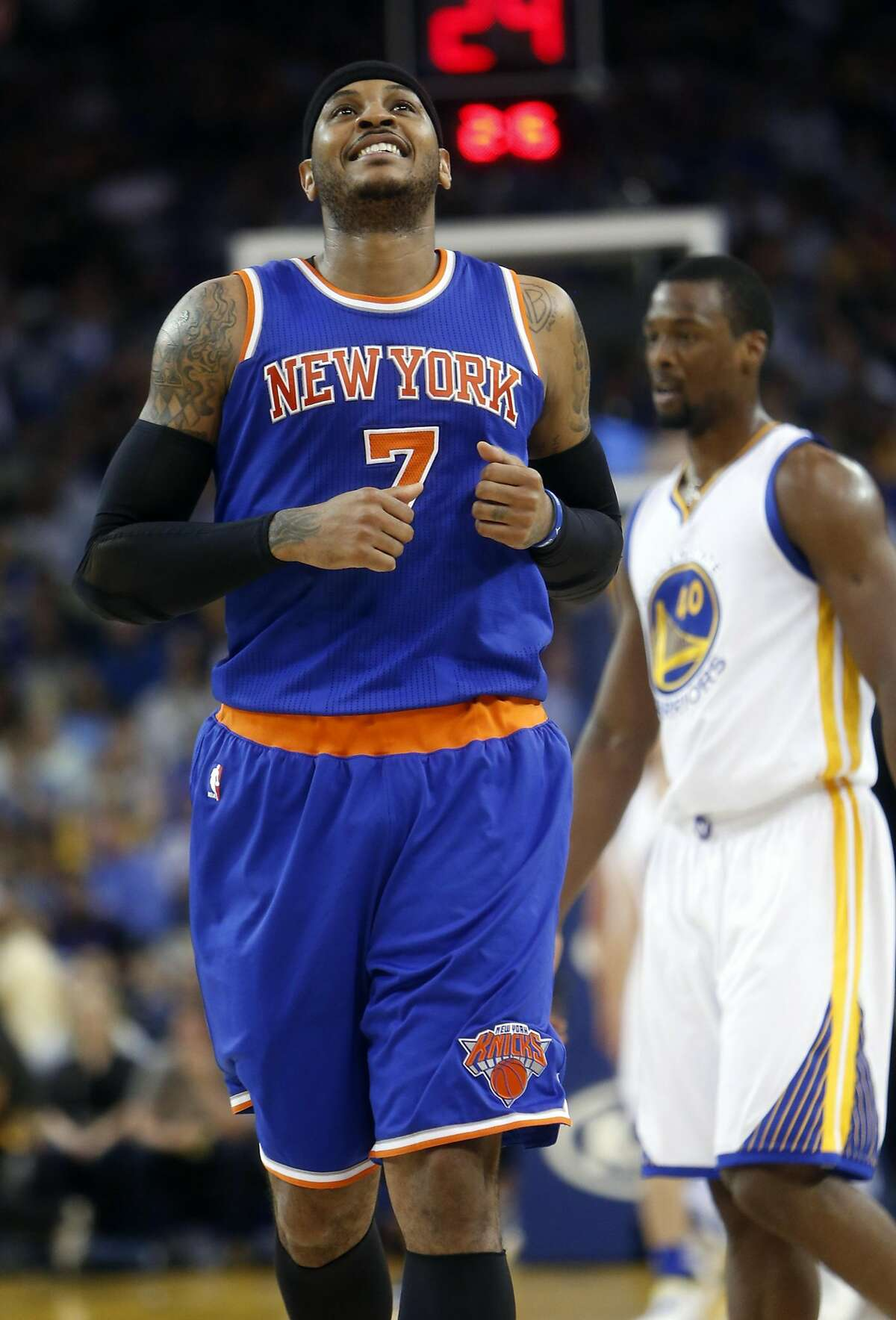 New York Knicks' Carmelo Anthony reacts to a successful 3-pointer in 2nd quarter against Golden State Warriors' Harrison Barnes in NBA game at Oracle Arena in Oakland, Calif., on Wednesday, March 16, 2016.