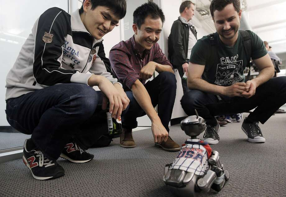 Kazu Komoto (left), Lawrence Leung and Justin Kuehn play with an Aibo robotic dog during the monthly Bots and Beer event put on by Silicon Valley Robotics. Photo: Carlos Avila Gonzalez, The Chronicle