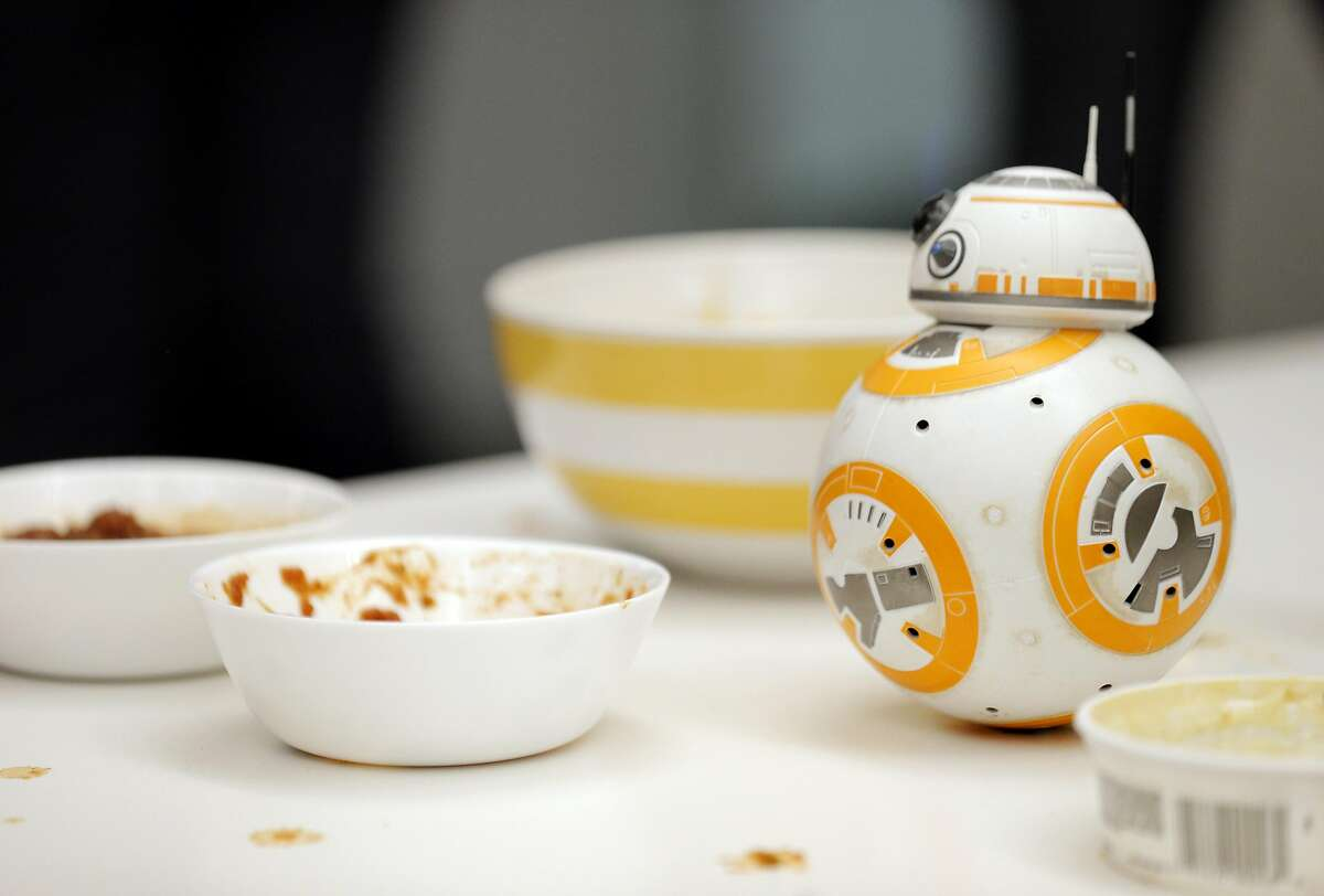 A BB-8 robot stands near the chips and dip during a social meetup of San Francisco's community of robot aficionados, and their robots put on by Silicon Valley Robotics at Comet Labs in San Francisco, Calif., on Wednesday, March 16, 2016.