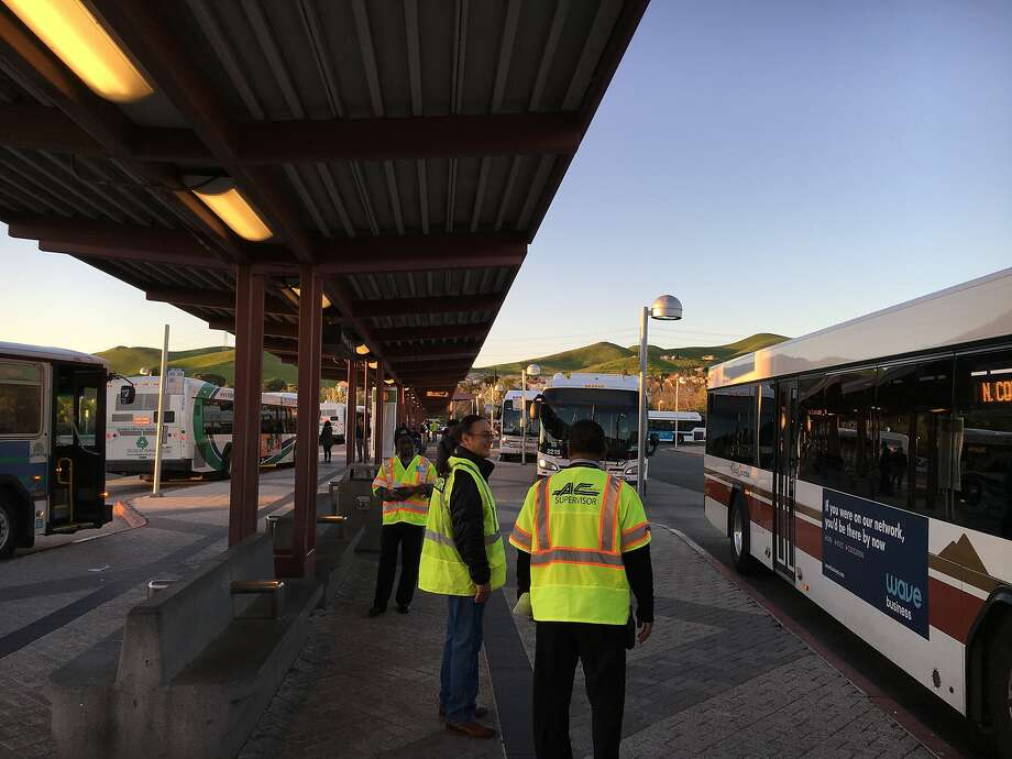BART workers stand ready to guide commuters to a bus-bridge as the transit agency heads into its second day of delays and halted service due to a track problem in the East Bay. Photo: Hamed Aleaziz