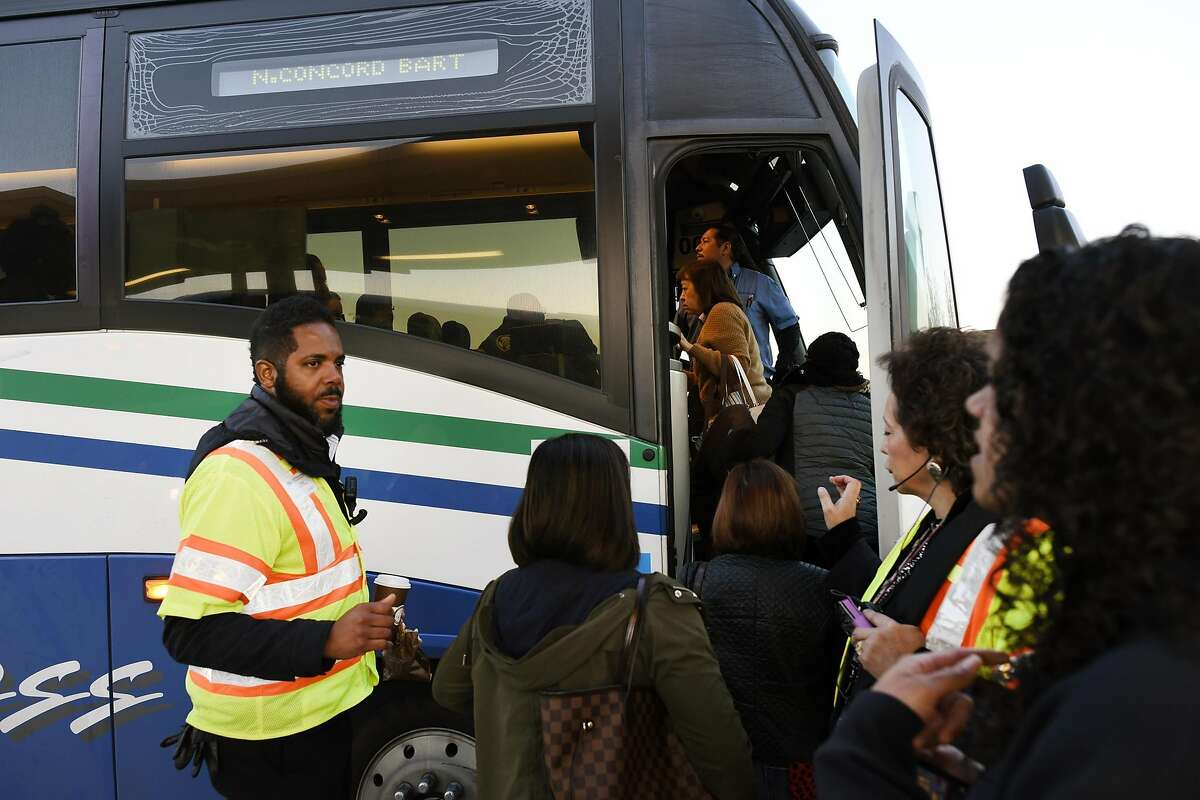 BART Transportation Supervisor Phaethon Brown, left, helps customers board a free shuttle bus at the Pittsburg/Bay Point BART station in Pittsburg, CA Thursday, March 17, 2016. Free shuttle bus service was offered as BART service was out between the Pittsburg/Bay Point and Concord stations due to an electrical problem.