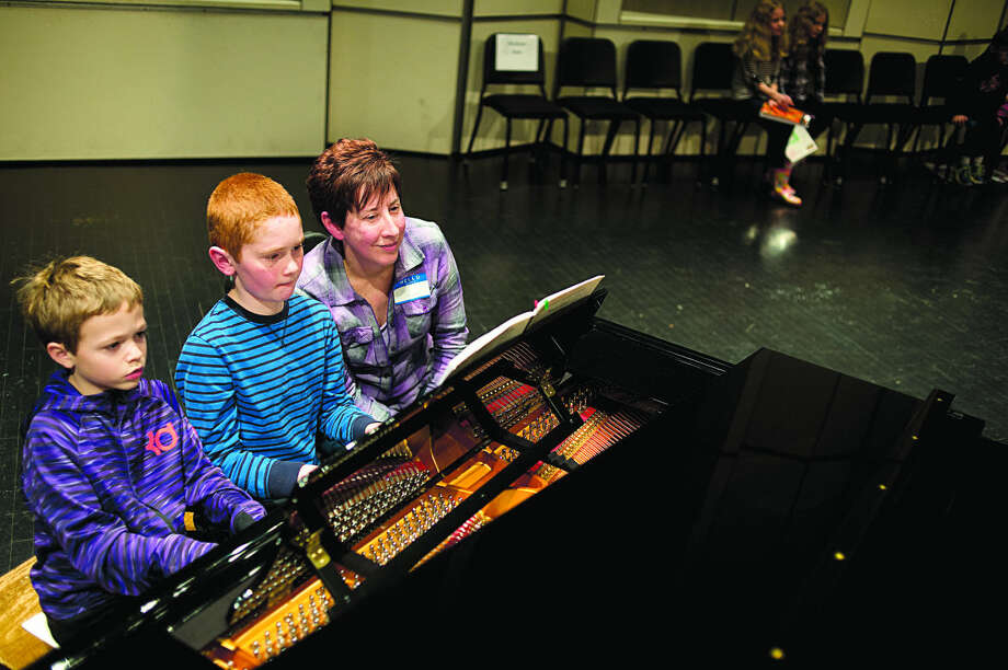 BRITTNEY LOHMILLER | blohmiller@mdn.net From left: 8-year-old Nathan Hansen and Matthew Koob, 10, practice playing the piano while their teacher Rae Vaught, all of Midland, follows the sheet music during the rehearsal for the KeyboardFest 2016 Friday evening at the Midland Center for the Arts. This annual event features approximately 250 Midland County piano students of various ages and skill levels performing selected pieces alongside their teachers. Under the direction of James Hohmeyer, students will perform four-handed duets. Photo: Brittney Lohmiller/Midland Daily News
