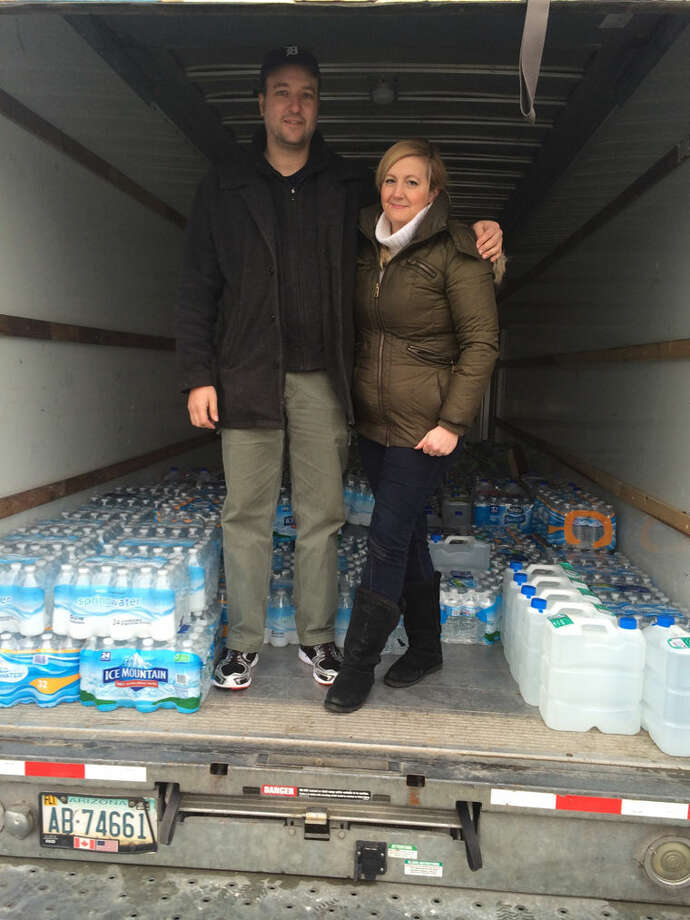 Jeff VandeZande and his girlfriend Jenn Barko are shown with one on the two truckloads of water they delivered to Flint.