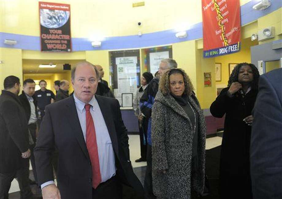 Detroit Mayor Mike Duggan, left, leaves Fisher Magnet Lower Academy in Detroit, Tuesday, Jan. 12, 2016, after talking with school administrators and Detroit Public Schools officials about the condition of the school. The visits occurred while two dozen schools were closed because of a sick-out by teachers who are upset about pay, class sizes, rodents and mold. Photo: Jose Juarez/Detroit News Via AP