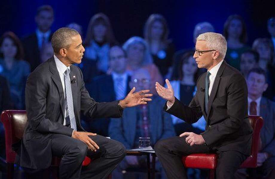 President Barack Obama, left, talks during a CNN televised town hall meeting hosted by Anderson Cooper, right, at George Mason University in Fairfax, Va., Thursday. Photo:  Pablo Martinez Monsivais | AP Photo
