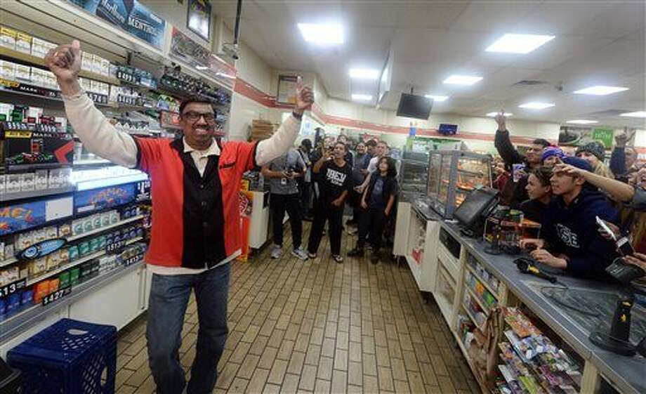 7-Eleven store clerk M. Faroqui celebrates after learning the store sold a winning Powerball ticket in Chino Hills, Calif. One winning ticket was sold at the store located in suburban Los Angeles said Alex Traverso, a spokesman for California lottery. The identity of the winner is not yet known. Photo: Will Lester | The Sun Via AP