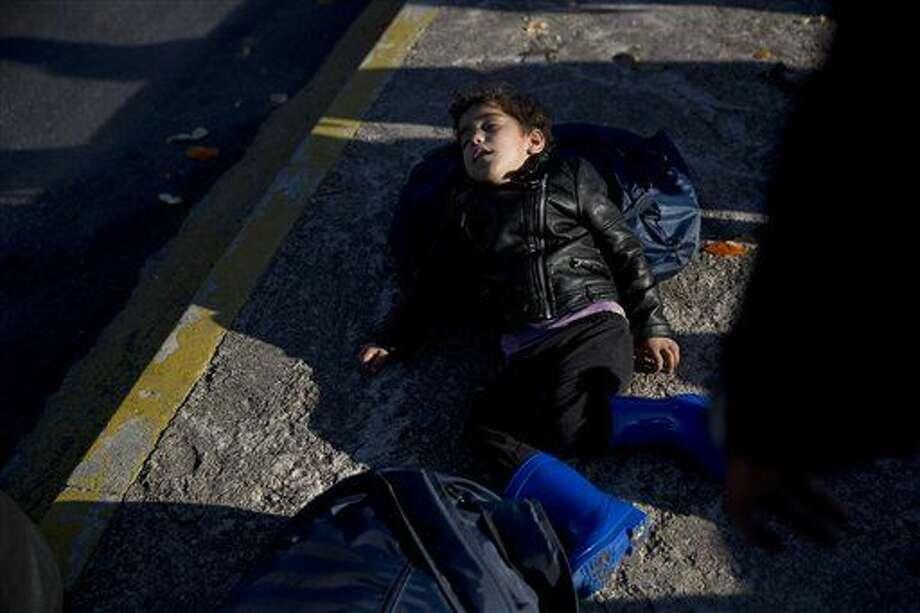 Una niña afgana duerme sobre el pavimento tras llegar junto con cientos de refugiados y migrantes al puerto de Piraeus, cerca de Atenas, el lunes 22 de febrero de 2015. (AP Foto/Petros Giannakouris) Photo: Petros Giannakouris
