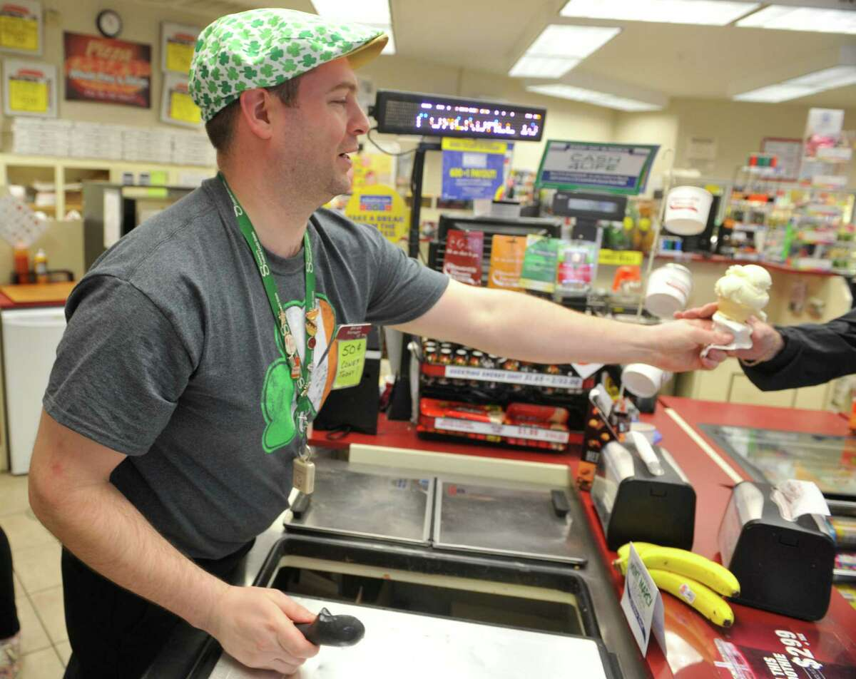 Store manager Brian Novak hands an ice cream cone to a customer at the Stewart's Shops on Thursday, March 17, 2016, in Fort Johnson, N.Y. Stewart's runs a promotion on St. Patrick's Day that if you wear something green you can get a single-scoop ice cream cone for 50 cents. (Paul Buckowski / Times Union)