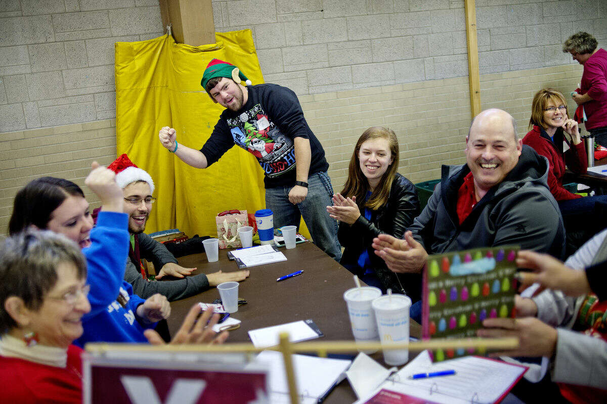 Clockwise from left, Judy Ruttan, Lacey Wright, Tyler Porter, Chase Brenske, Kylie Anderson and Mike Coleman cheer after receiving a gift during this year's United Way of Midland County Sharing Tree distribution day at Blessed Sacrament Church. The group represented The ROCK Center for Youth Development.