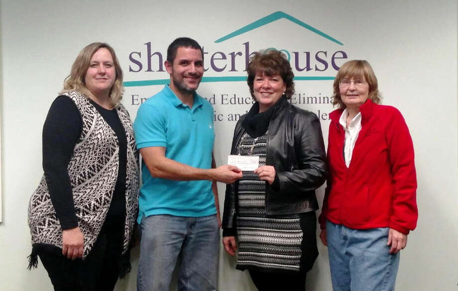 Michael Spencer, second from left, presents a check in the amount of $2,188 from the Judy V. Spencer fund to Janine Ouderkirk, executive director of Shelterhouse, during a recent meeting at the Midland non-profit organization. Robin Greiner, shelter services director for Shelterhouse, far left, and Joann Taylor, president of Midland's SOS Animal Rescue, far right, also participated in the check presentation. Photo: Photo Provided