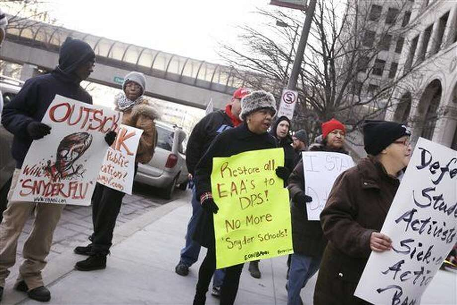 Protesters stand outside Cadillac Place, Monday, Jan. 25, 2016 in Detroit, where a judge is hearing arguments in a case that could force teachers to stop skipping school. The teachers' so-called sick-outs have repeatedly forced the district to close schools during the past two weeks, keeping thousands of students at home, so in a bid to stop the absences, the district filed a lawsuit. Teachers are upset over pay, class sizes, building conditions and Gov. Rick Snyder's plan to overhaul the district. Photo: AP Photo/Carlos Osorio