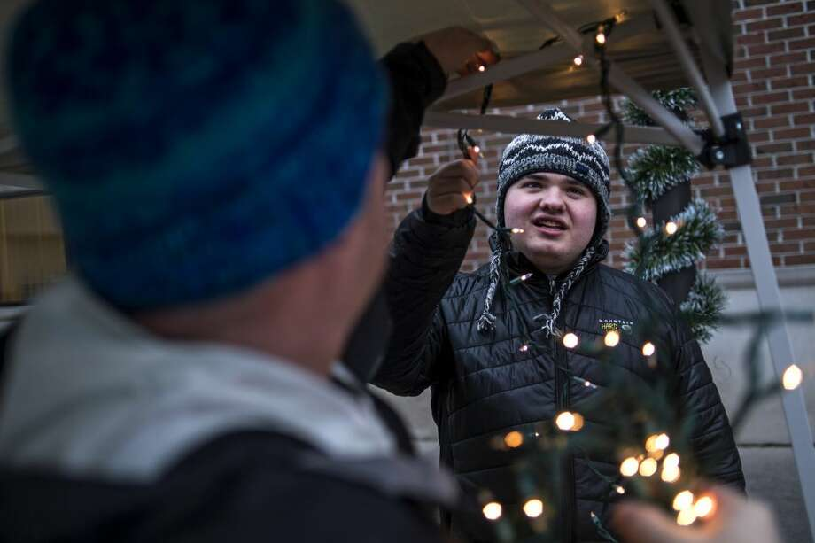 Dennis Mashue, left, strings lights through their booth at Midland's Winter Village as son Tucker Mashue, 17, right, helps on Dec. 17. Together Dennis and Tucker Mashue Tuck's Tooques, a pro-autism microbusiness, which helps Dennis teach Tucker entrepreneurship skills by selling handmade Nepalese winter hats. Photo: Erin Kirkland | Midland Daily News