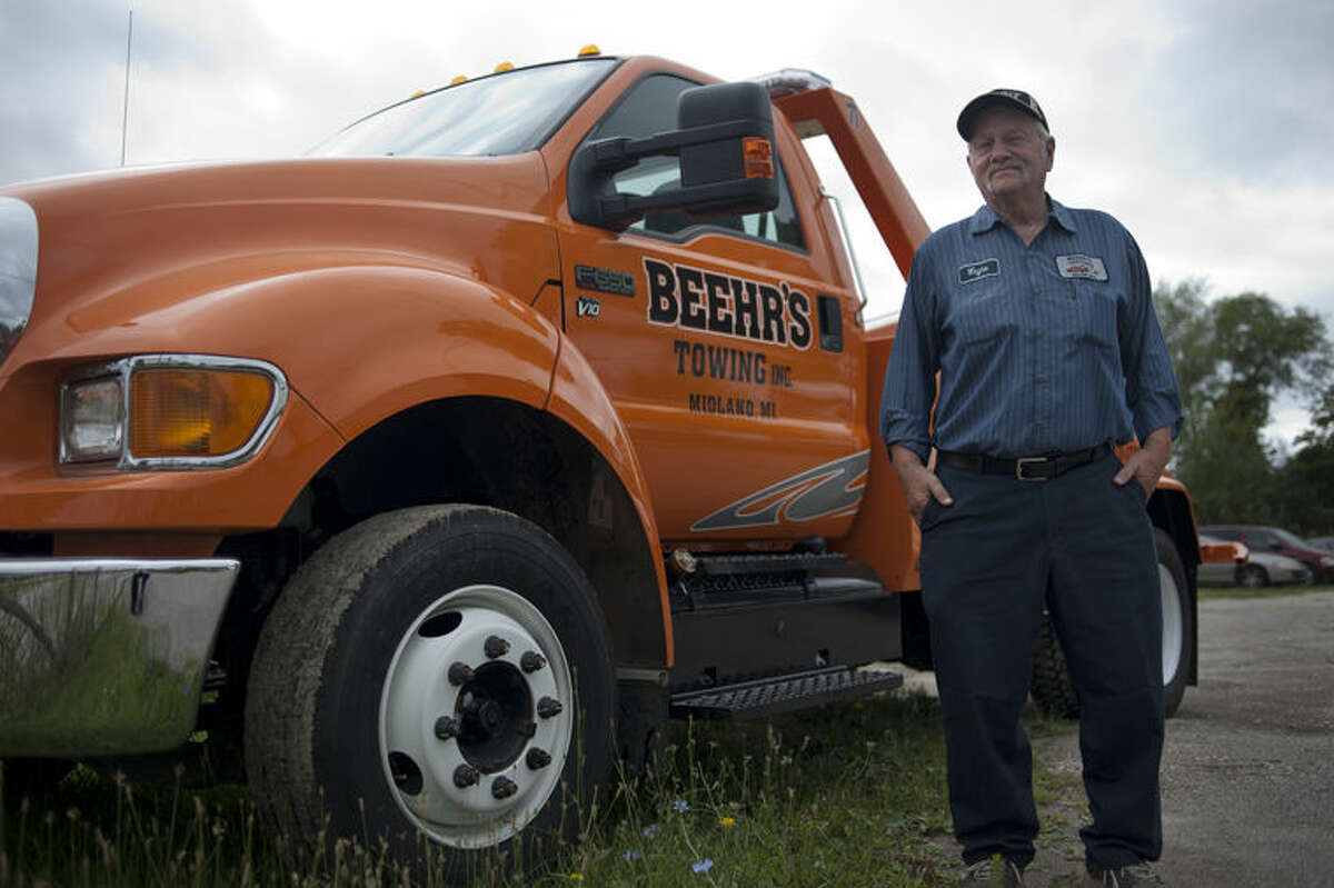 The late Wayne Beehr is shown standing by a Beehr's Towing truck.