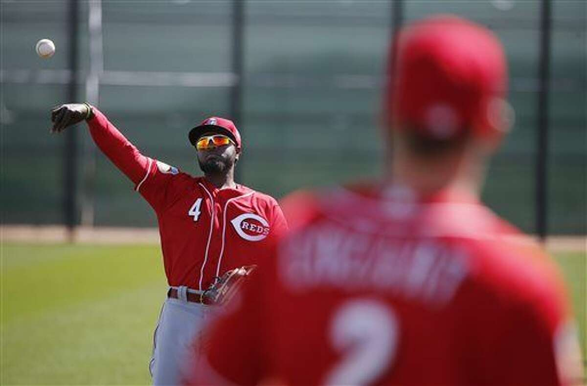 Cincinnati Reds' Brandon Phillips (4) warms up with Zack Cozart, right, during a spring training baseball workout Tuesday, Feb. 23, 2016, in Goodyear, Ariz. (AP Photo/Ross D. Franklin)