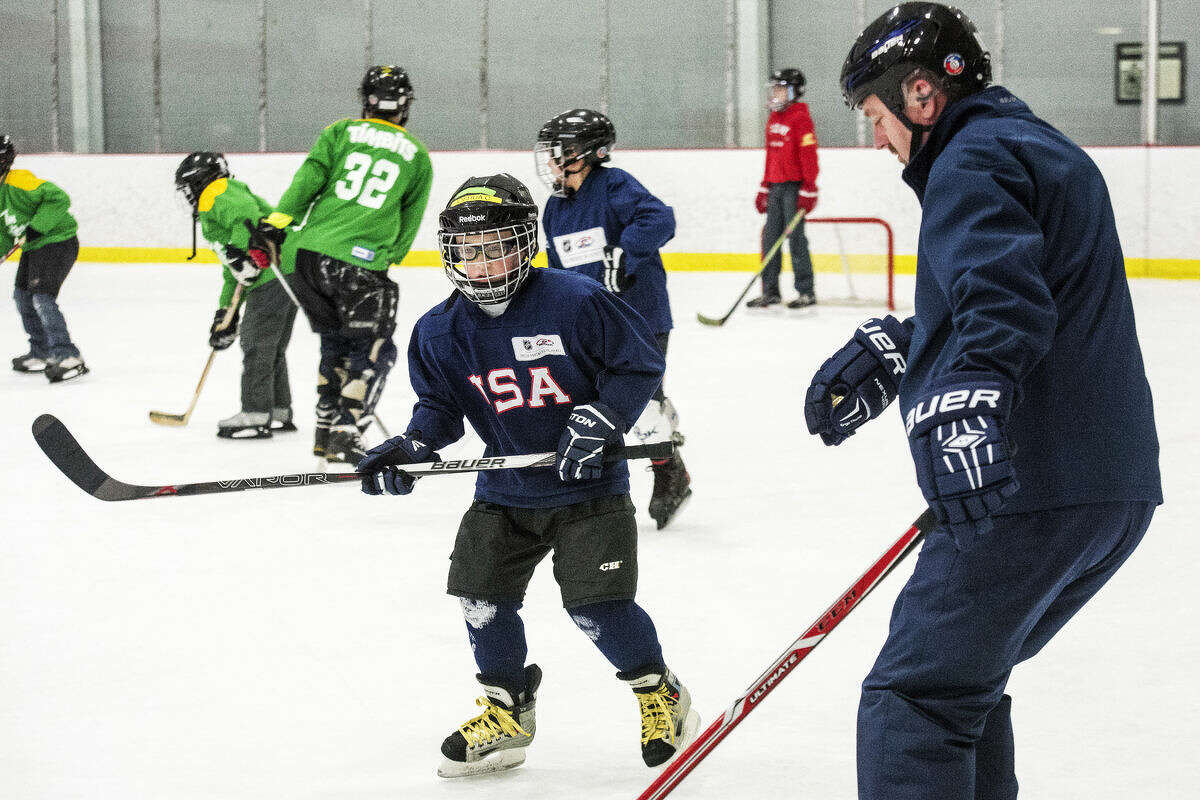 Joshua Carlson, 8, of Freeland, practices how to stop with his dad, volunteer Peter Carlson, during Try Hockey for Free Day, an event recently hosted by the Midland Amateur Hockey League at the Midland Civic Arena.