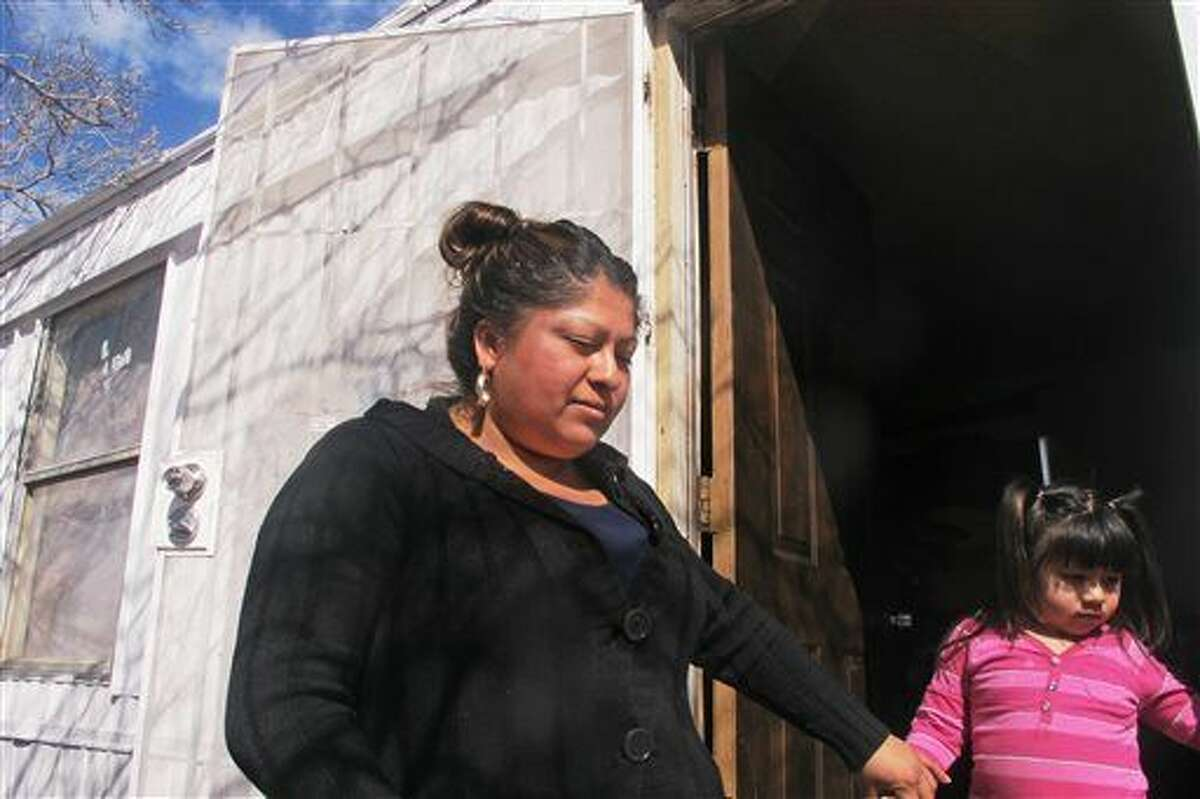 Grisel Alvarado, left, stands on the front stoop of an Albuquerque, N.M., home Monday, Feb. 22, 2016, where her nephew, Edgar Camacho-Alvarado, was fatally shot Saturday, Feb. 20, as federal marshals sought to execute an arrest warrant for another man. Family members were gathered at the home two days after the shooting that they say happened as Camacho-Alvarado was repairing his pickup truck. (AP Photo/Mary Hudetz).