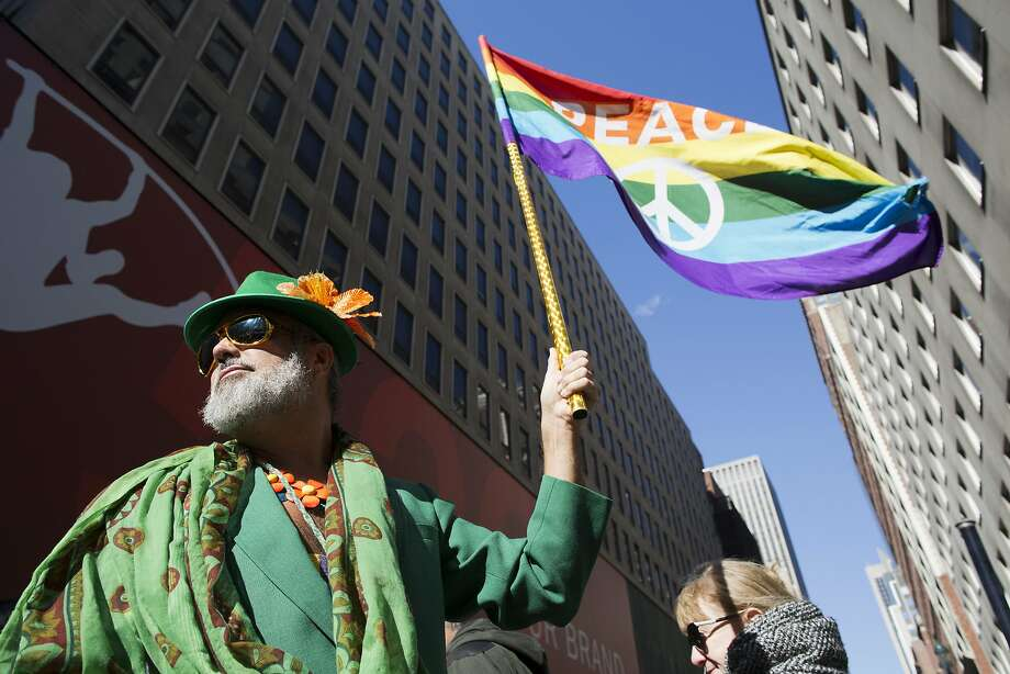 Steven Menendez waves a gay pride flag as he waits for the nation's largest St. Patrick's Day parade to begin on Fifth Ave. Photo: Mary Altaffer, AP