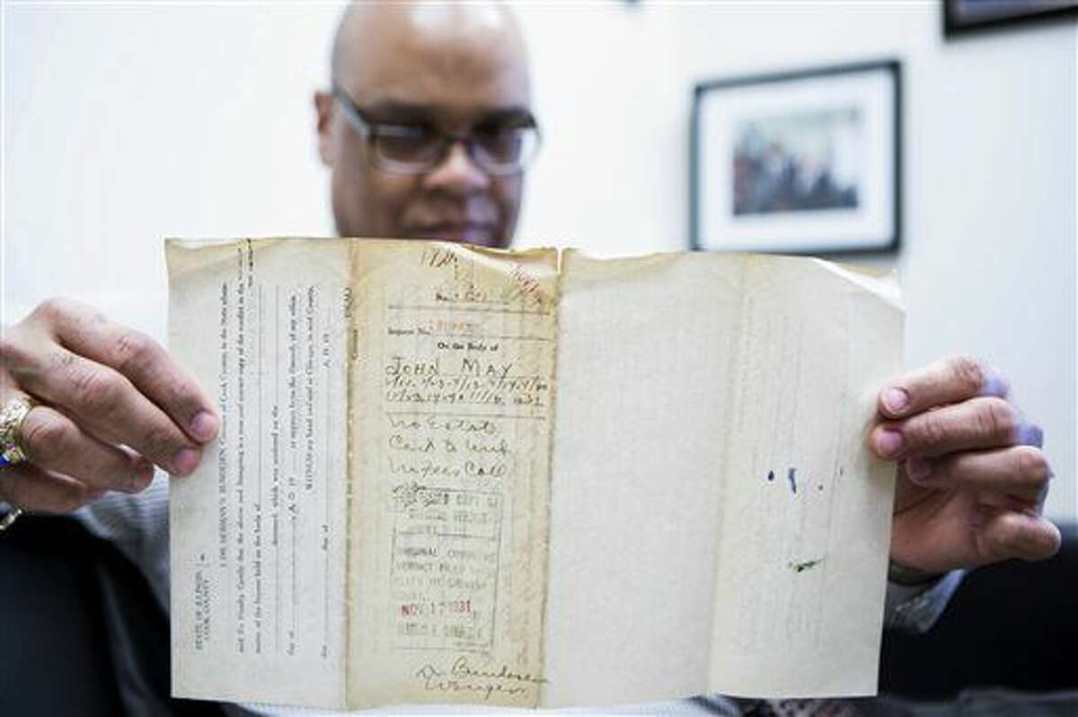 In this Thursday, Feb. 11, 2016 photo, James Sledge, an executive officer at the Cook County Medical Examiner's office in Chicago, holds one of the original autopsy reports from the infamous Valentine's Day massacre 87 years ago. Sledge, a local history buff, asked if he could look at the reports from the attack that left seven men dead in a Chicago garage and widely believed to have been ordered by Al Capone. Sledge's staff made multiple trips to a government warehouse before they found the papers in a metal file cabinet. (James Foster/Chicago Sun-Times via AP) CHICAGO TRIBUNE OUT, MANDATORY CREDIT, MAGS OUT, NO SALES
