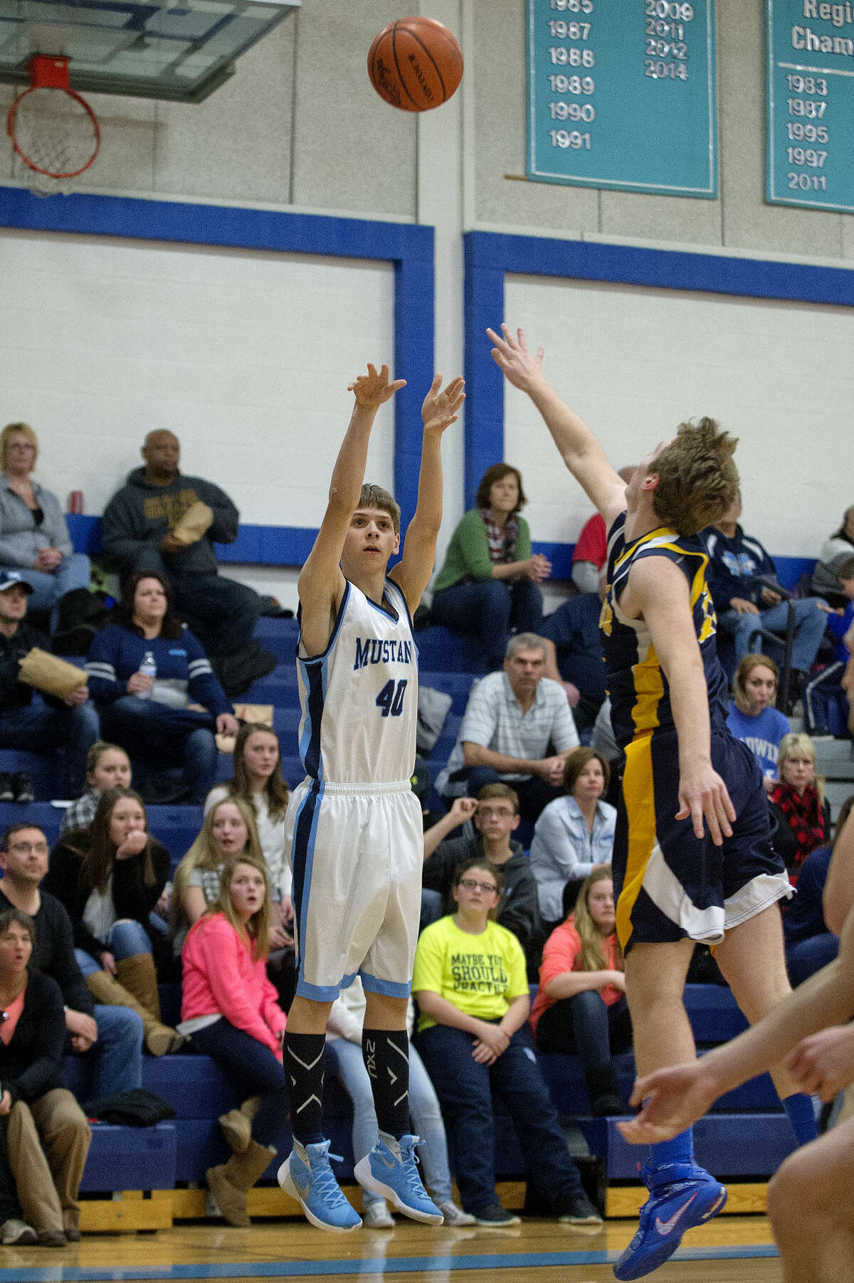 Meridian's Lucas Lueder shoots a 3-pointer as Roscommon's Kaleb Keipert defends during the first half on Tuesday at Meridian High School.