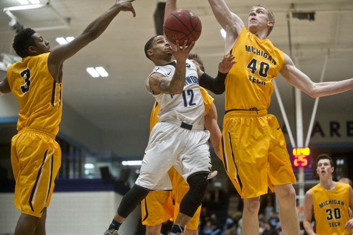In this 2016 file photo, Northwood's Maurice Jones goes up for a layup as Michigan Tech's Miles Sigh, left, and Kyle Stankowski, right, try to block him at Northwood University's Riepma Arena.
