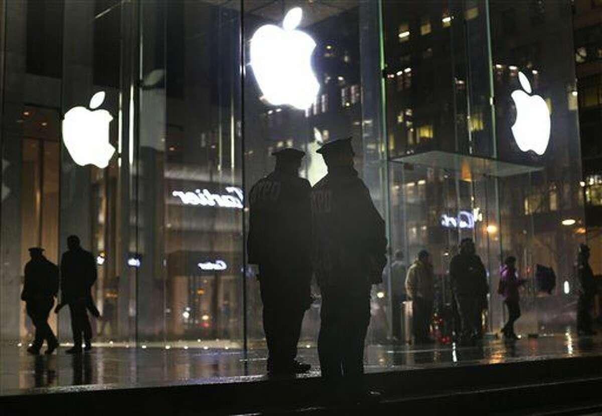 Agentes de policía montan guardia frente al comercio de Apple en Nueva York durante una manifestación el 23 de febrero del 2016 en Nueva York. Apple Inc. se aprestaba a decirle a fines de febrero del 2016 a un juez federal que su disputa con el FBI acerca del acceso a un iPhone codificado debería ser decidida por el Congreso y no por la justicia, según se enteró The Associated Press. (AP Foto/Julie Jacobson)